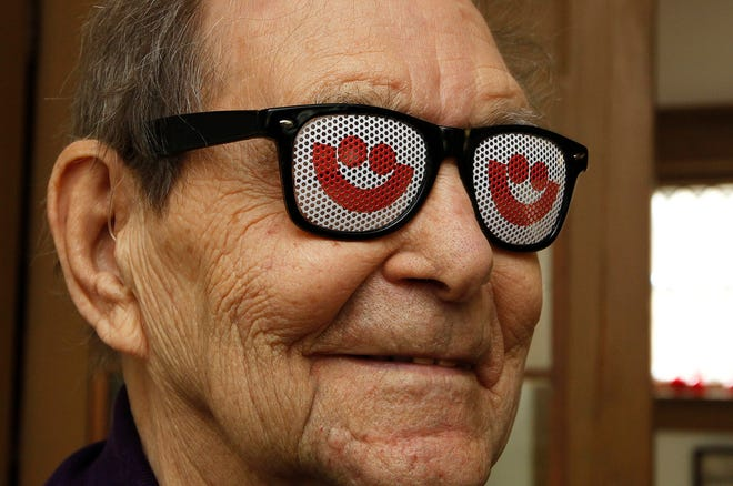 """Noel Spangler tries on a pair of Summerfest glasses given to him by Summerfest staff at Spangler's home, one of several gifts for his 90th birthday in 2013. Spangler was responsible for designing the """"smiley face"""" Summerfest logo back in 1970. Spangler died Dec. 28 at 97."""