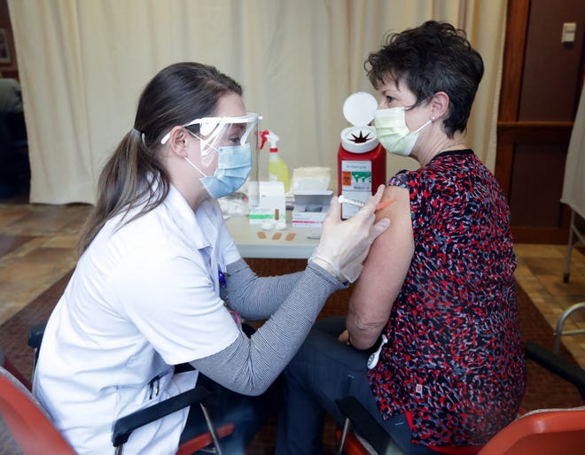 Walgreens pharmacist Erika Medlock, left, administers a COVID-19 vaccine to nurse Celeste Klaus as Shorehaven's nursing home residents and staff received their first dose of the Moderna vaccine at the facility in Oconomowoc Monday.