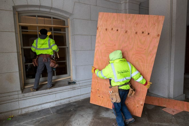 "Employees with Daniels General Contractors board up ground-floor and other easily accessible windows Monday, Jan. 11, 2021, at the Capitol in Madison, Wis. ""In keeping with proactive cautionary measures happening at statehouses throughout the country, the Department of Administration's Facilities Management team will be boarding exterior ground-floor windows at the State Capitol beginning today,"" says  Molly Vidal, spokeswoman for the state Department of Administration."