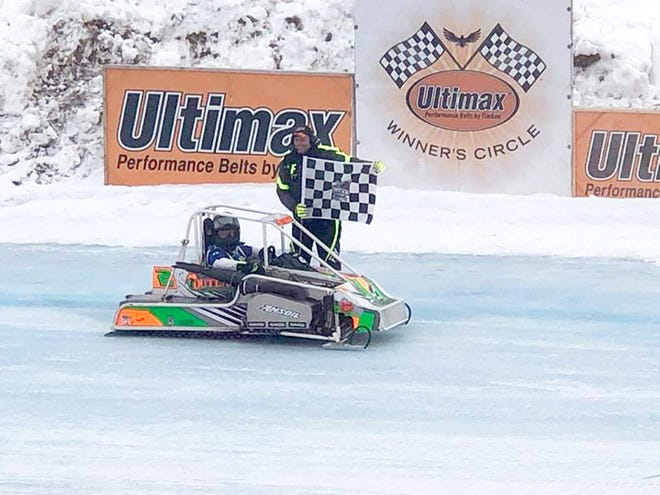 Rich Bickle picks up the checkered flag after winning the Outlaw 600 feature at the Vintage World Championship Snowmobile Races on Sunday in Eagle River.