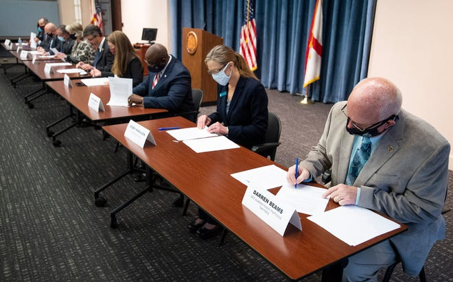 Darren Beams, of the West Alabama Human Trafficking Task Force, right, and others sign an agreement as Alabama Attorney General Steve Marshall announces the formation of a Human Trafficking Task Force during a news conference in Montgomery, Ala., on Monday January 11, 2021.