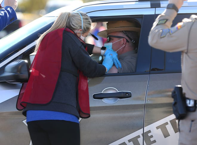 A worker gives a COVID-19 vaccine to an Arizona Department of Public Safety trooper during a test run at the state's first 24/7 COVID-19 vaccination site on Jan. 11, 2021, at the State Farm Stadium in Glendale.