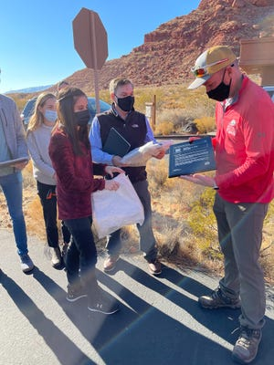 Jason Pitts, SUU research fellow for outdoor pathways, and DSU and SUU students and alumni present Gov. Spencer J. Cox with a ParksPass plaque at Snow Canyon State Park, date unknown.