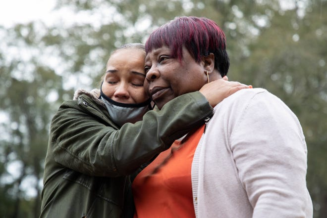 Claudette Mills, right, hugs her neighbor Rochelle Hanley as she cries in the front yard of Mills' burned home Monday, Jan. 11, 2021. As Mills discovered the fire inside her living room Saturday night, she ran outside where Hanley, who was out walking her dog, helped her call 911.