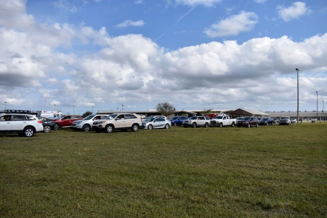 Cars line up in the medical observation area at a COVID-19 vaccination clinic Monday, Jan. 11, 2021, at the St. Lucie County Fairgrounds in Fort Pierce, Fla. About 4,500 seniors ages 65 and older were expected to receive the Pfizer/BioNTech vaccine during the three-day event, said Clint Sperber, administrator of the Florida Department of Health in St. Lucie.