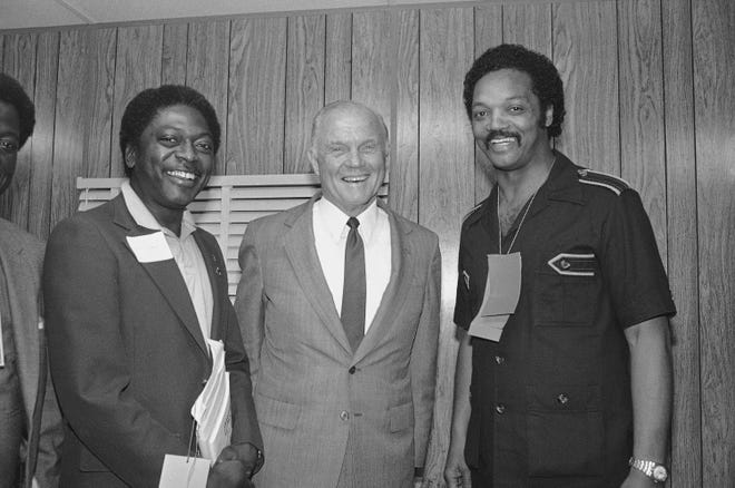 Sen. John Glenn of Ohio, center, meets with Rev. Jesse Jackson of Chicago, right, and Jim Clyburn of South Carolina in his trailer at the Philadelphia Civic Center during the Democratic National Party Conference, Saturday, June 26, 1982, Philadelphia, Pa.