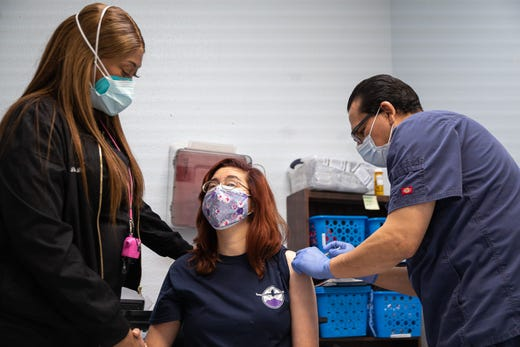 Gabriel Fernandez, a registered nurse from Texas Tech University Health Sciences Center El Paso, injects a COVID-19 vaccine into the arm of an Emergence Health Network client with developmental disabilities at the EHN DayHab center in East El Paso on Jan. 7, 2021.