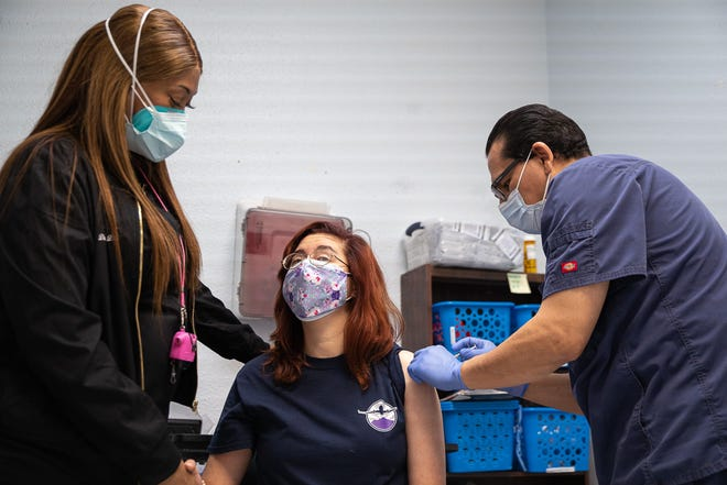 Gabriel Fernandez, a registered nurse from Texas Tech University Health Sciences Center El Paso, injects a COVID-19 vaccine into the arm of an Emergence Health Network client with developmental disabilities at the EHN DayHab center in East El Paso, Texas, on Jan. 7, 2021.