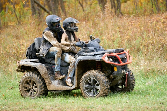 Already muddy, Matt and Bri mount an ATV before it topples over, depositing them into a mud puddle.