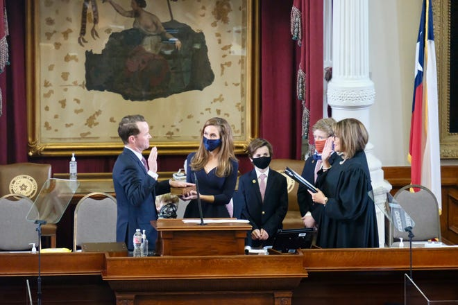 Rep. Dade Phelan, R-Beaumont, takes the oath of office after being elected Texas House speaker on Tuesday. Wife Kim Phelan held the Bible and Texas Supreme Court Justice Eva Guzman administered the oath. The House unanimously approved rules Thursday for how to govern during the coronavirus pandemic.