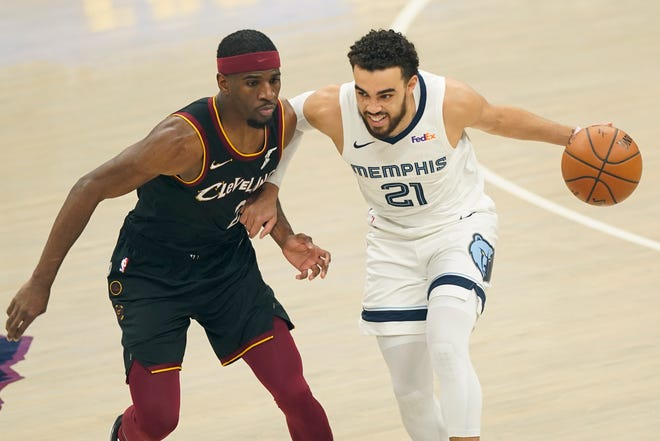 Memphis Grizzlies' Tyus Jones, right, drives past Cleveland Cavaliers' Damyean Dotson in the first half of an NBA basketball game, Monday, Jan. 11, 2021, in Cleveland. (AP Photo/Tony Dejak)