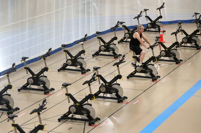 A lone man rides an exercise bike Saturday at the Tallmadge Recreation Center. Several area gymsand fitness studios have not seen the big January influxthey normally do as people continue to be hesitant to exercise in indoor congregant settings.