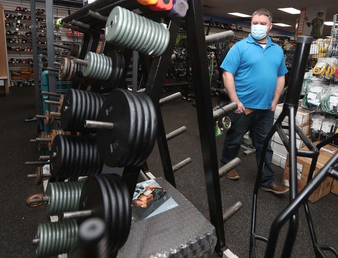 Matt Trayer, manager of Play It Again Sports, walks next to the display of weights that is half empty because they are in short supply at the store on Howe Avenue in Cuyahoga Falls.  Trayer said many people are continuing to work out at home after spending money on at-home gyms during the pandemic.