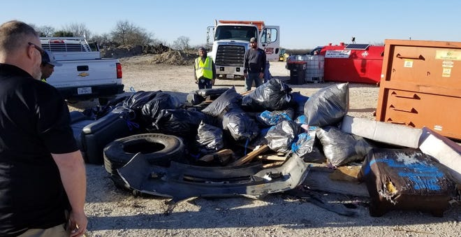 """Anna Public Works employees examine items found during its December """"Trash Bash"""""""