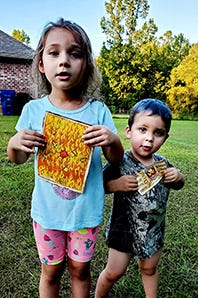 "Lucine (left) and Levi (right) hold their ""treasure maps"" on a hot, Louisiana summer day in 2019. Their dad, Gregory, hid random treats in the yard and created an adventurous game for the kids to enjoy."