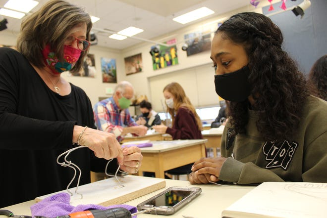 Sculptor Pamela Winters, left, shows BHS art student Sariah Monfared how to begin a sculpture by shaping a wire armature.