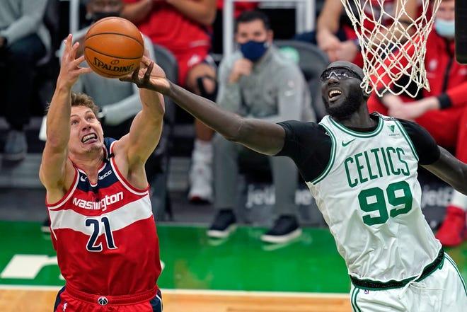 Washington Wizards center Moritz Wagner (21) and Boston Celtics center Tacko Fall (99) reach for a rebound during the second half of an NBA basketball game, Friday, Jan. 8, 2021, in Boston. (AP Photo/Elise Amendola)