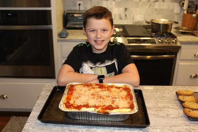 Travis Amero, 11, with a lasagna he helped make with his grandmother, Nancy Johnson of Brewster, Cape Cod coordinator for Lasagna Love. The nonprofit donates a hot meal once a month to a neighbor who needs a break.