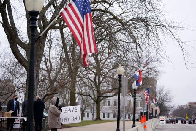 A person holds a sign outside the Missouri Capitol before the start of inauguration ceremonies Monday in Jefferson City.