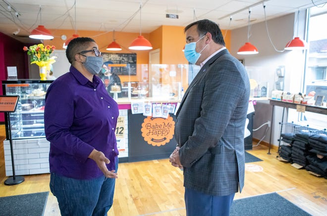 Bake Me Happy co-owner Letha Pugh talks to Columbus Mayor Andrew Ginther inside the Merion Village shop on Tuesday, Jan. 12, 2021. The store was forced to close over the weekend due to racial threats of violence.