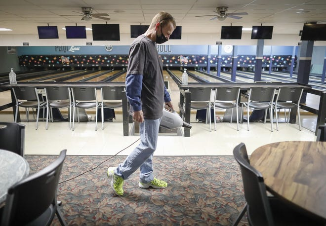 Operation Manager Eddie Lanham uses an industrial disinfecting machine to clean the carpets at Penn Lanes bowling alley in Delaware. In addition to thorough cleaning of lanes, shoes and bowling balls after each group is done, the alley also asks patrons to practice safe health protocols such as social distancing.