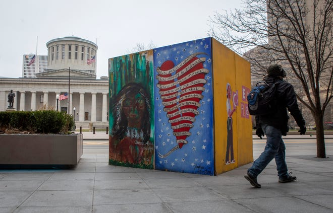 A pedestrian walks past artwork painted on plywood that was used to cover the front of the Huntington Building across the street from the Ohio Statehouse in Columbus on Tuesday. Much of the downtown area was boarded up following damage caused by protests over the summer, but the plywood window coverings have slowly gone away. Local officials asked people to stay away from Downtown through Wednesday.
