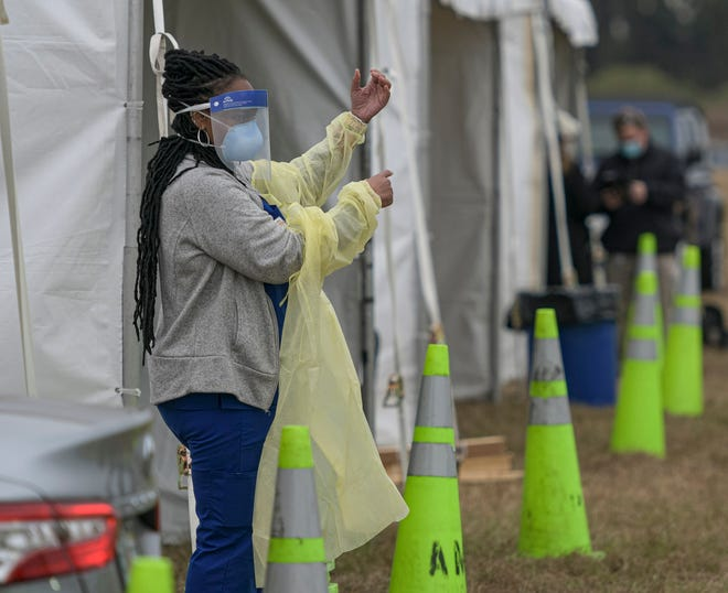 A health care worker puts on a protective gown at a COVID-19 vaccination site in The Villages on Tuesday, Jan. 12, 2021. [PAUL RYAN / CORRESPONDENT]