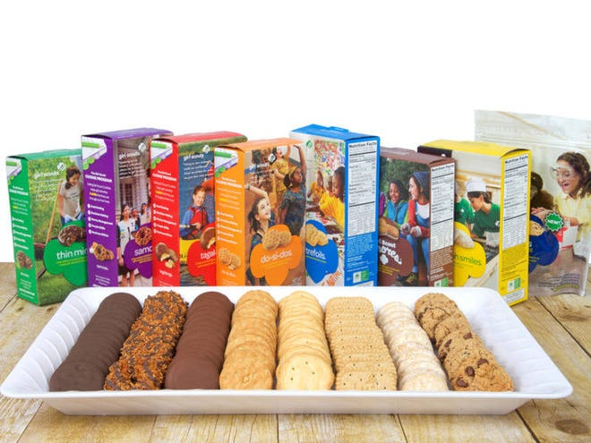 Alameda, CA - September 16, 2017: White tray with 8 varieties of Girl Scout Cookies on a wood table, boxes standing behind plate. Available annually during Girl Scout cookie sales from ABC Bakers; Shutterstock ID 716908615; Notes:
