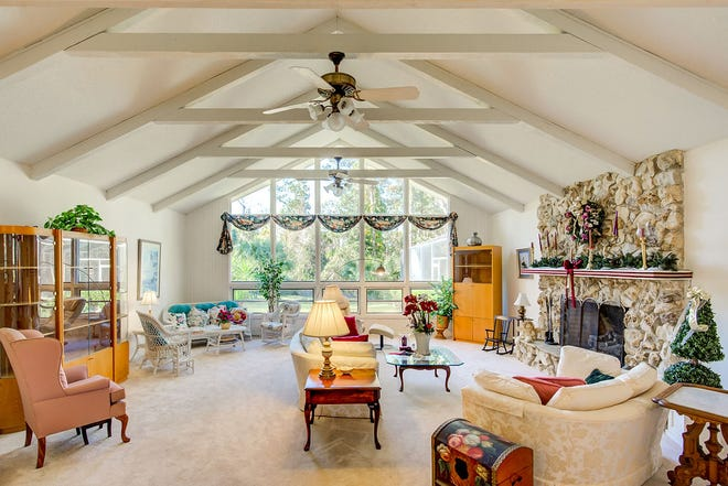 The living room of this Ormond Beach home features a vaulted-and-beamed ceiling, A-frame, floor-to-ceiling windows along the back wall and a massive brick fireplace.