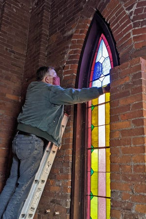 Heritage Trust board member Steve Rowland removes a Gothic stained glass window from the tower at Monmouth's First United Methodist Church, built in 1889