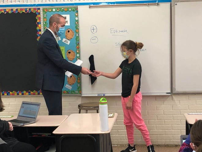 Dr. Adam Brumbaugh, Superintendent of Geneseo Schools, presents a Maple Leaf Medallion to Jaylee Brudos, a fifth grader in the Geneseo School District