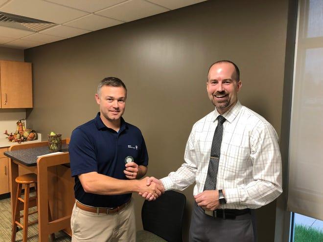 Joe Nichols, left, athletic director at Geneseo High School, receives a Maple Leaf Medallion from Dr. Adam Brumbaugh, Geneseo Superintendent of Schools.