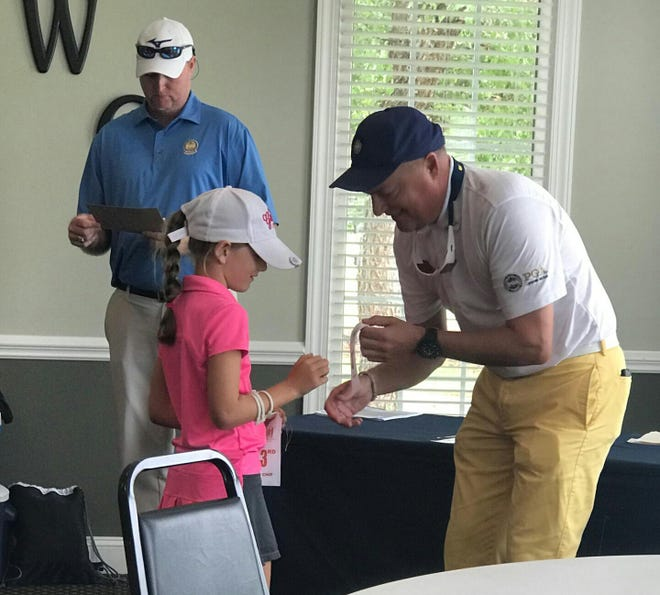Fletcher's Brett Miller, right, presents a ribbon to a young golfer recently.