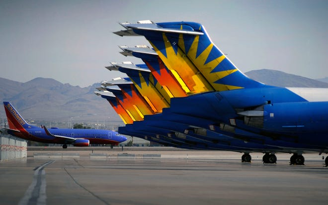 In this May 9, 2013, photo, a Southwest airline taxis by parked Allegiant Air jetliners at McCarran International Airport in Las Vegas. While other U.S. airlines have struggled with the ups and downs of the economy and oil prices, tiny Allegiant Air has been profitable for 10 straight years.