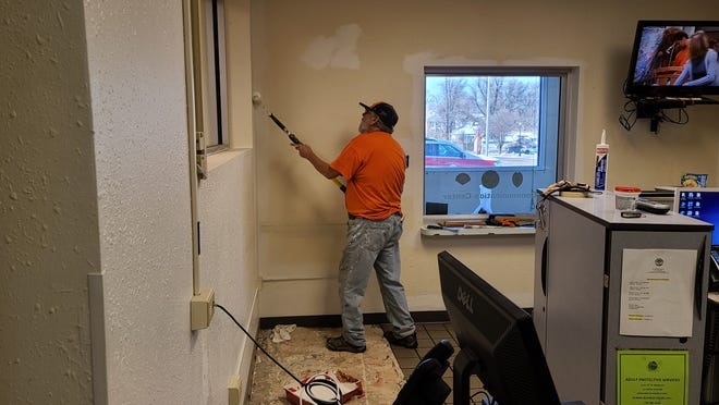 La Junta painter Jerry Gonzales slides a paint roller up one wall of the La Junta dispatch center.