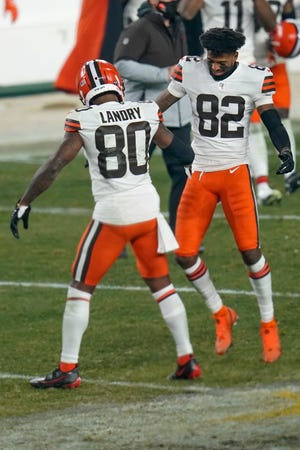 Cleveland Browns wide receivers Jarvis Landry (80) and Rashard Higgins (82) celebrate after defeating the Pittsburgh Steelers in an NFL wild-card playoff football game, late Sunday, Jan. 10, 2021, in Pittsburgh.