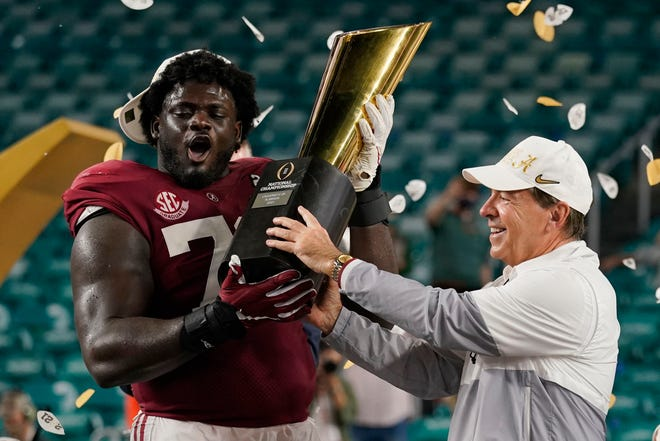 Alabama head coach Nick Saban and offensive lineman Alex Leatherwood hold the trophy after their win against Ohio State in an NCAA College Football Playoff national championship game, Tuesday, Jan. 12, 2021, in Miami Gardens, Fla. Alabama won 52-24.