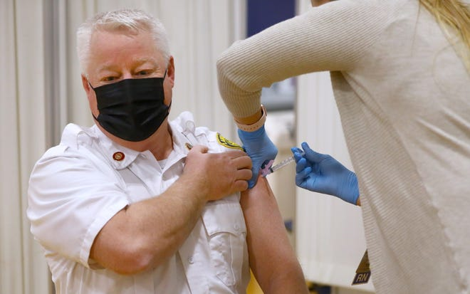 Lawrence Fire Deputy Chief Bob Wilson is the first to receive the vaccination, which is administered by RN Leila Volinsky, service line operations manager for Lawrence General Hospital. [Pat Greenhouse/Pool, Globe Staff]