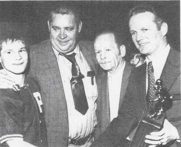 Pope John head wrestling coach Dale Kobler, second from right, stands with, from left, Mike Frick, assistant coach Barry Vandermark and the state tournament director after Frick won his third straight state title in 1972.