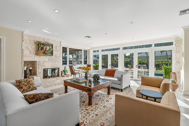 With its fireplace, the great room at 2243 Ibis Isle Road E. has a bank of glass doors that lead onto the lakefront patio. The three-bedroom house is listed for sale at $5.25 million.