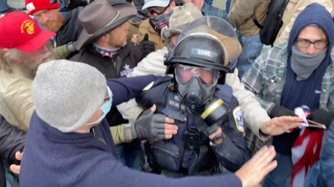 In an image provided by Jarrett Robertson, supporters of President Donald Trump are seen pulling at an officer during a violent attempt to breach the U.S. Capitol in Washington on Jan. 6, 2021. One of the most intense scenes of violence occurred during a struggle to breach a west-side door, during which multiple rioters dragged police officers out of a formation and assaulted them while they were trapped in the crowd.