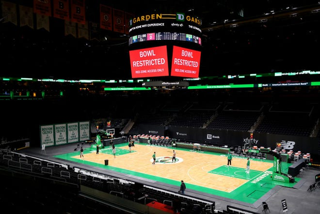 Players warm up on the court at TD Garden on Sunday, before the scheduled Celtics-Heat game that was called off because of COVID-19 concerns. Boston's last three games have now been postponed because of the virus.