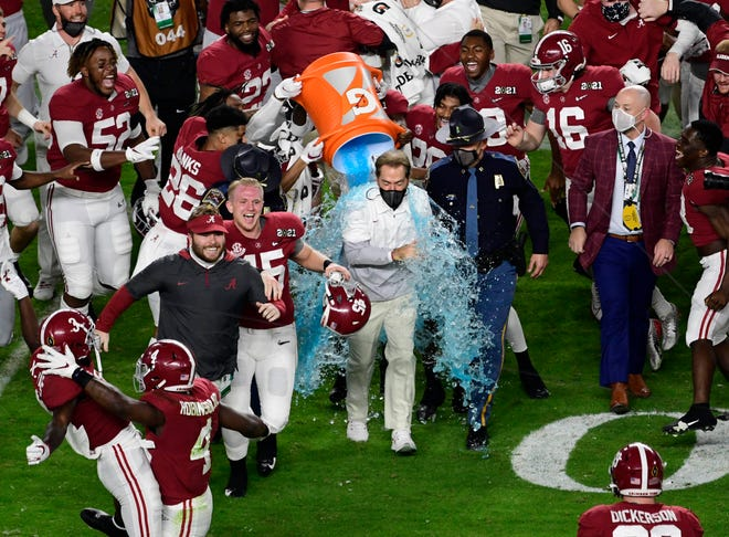 Alabama Crimson Tide head coach Nick Saban is dunked with Gatorade after defeating the Ohio State Buckeyes in the 2021 College Football Playoff National Championship Game at Hard Rock Stadium.