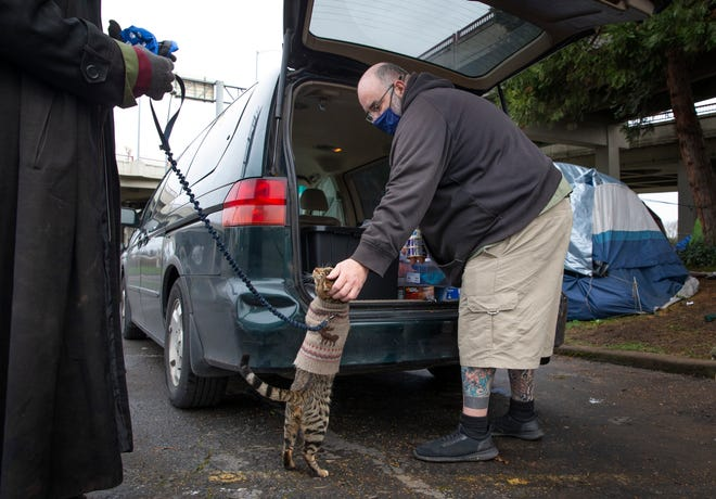 Jessie Joyner says hello to Oblio the cat during a meeting with his human at a campsite in Eugene to hand off pet supplies.
