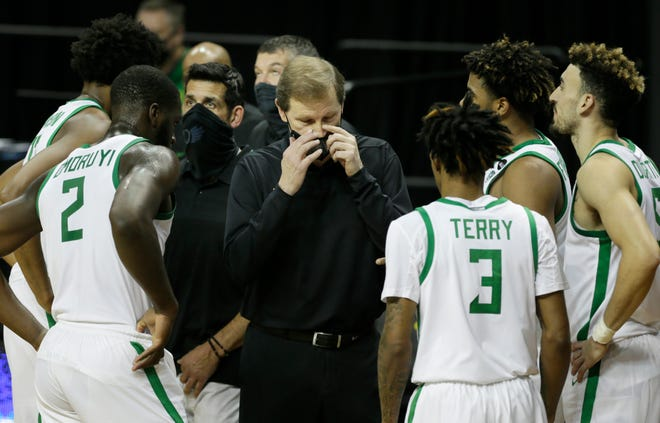 Oregon coach Dana Altman, center, adjusts his mask during a timeout against Eastern Washington in December.
