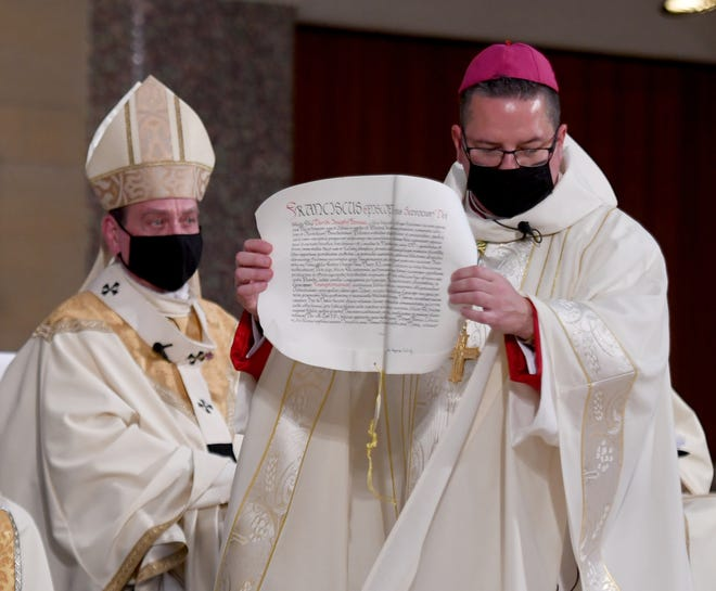 Bishop Elect David J. Bonnar shows the apostolic letter from Pope Francis.