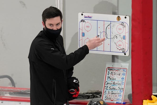 Chicago Blackhawks head coach Jeremy Colliton sets up a drill during an NHL hockey training camp practice Jan. 4 in Chicago.