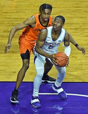 Kansas State guard Rudi Williams looks to score under the basket against Oklahoma State's Rondel Walker on Saturday at Bramlage Coliseum in Manhattan.