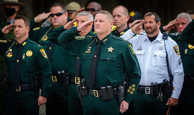 St. Johns County Sheriff Rob Hardwick, center, salutes with a group of law enforcement officers on Tuesday during the annual memorial service to remember Deputy Beach Marshal Ron Parker who was shot and killed on duty on Jan. 12, 1975, in St. Augustine Beach. The event took place in the Ronald Parker Memorial Park in the city.