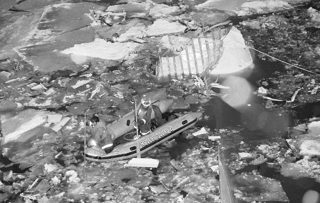 Rescue personnel in a raft try to find people that were in the wreckage of the Air Florida jetliner that crashed into the Potomac River after take-off from National Aircraft in Washington on Jan. 13, 1982.